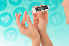 Composite image of diabetic woman using blood glucose monitor Royalty Free Stock Photo