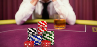 Composite image of dice with stack of colorful casino tokens Stock Image