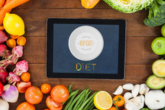 Composite image of diet new years resolution. Diet new years resolution against digital tablet surrounded with fresh vegetables royalty free illustration