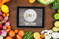 Composite image of diet new years resolution. Diet new years resolution against digital tablet surrounded with fresh vegetables stock illustration