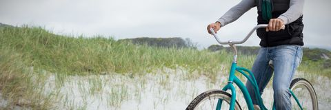 Composite image of digital composite of handsome man on a bike ride. Digital composite of handsome man on a bike ride against view of sand royalty free stock image