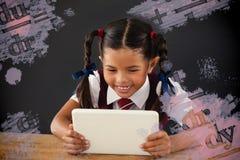 Composite image of digital composite image of equations. Digital composite image of equations against schoolgirl using digital tablet against blackboard Royalty Free Stock Image