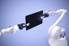Composite image of digital generated image of robots holding computer tablet 3d Royalty Free Stock Image