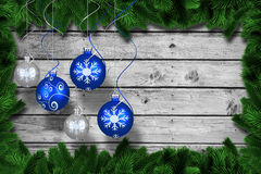 Composite image of digital hanging christmas bauble decoration. Digital hanging christmas bauble decoration against fir tree branches forming frame Stock Image