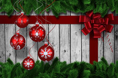 Composite image of digital hanging christmas bauble decoration. Digital hanging christmas bauble decoration against fir tree branches forming frame Royalty Free Stock Photo