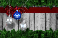 Composite image of digital hanging christmas bauble decoration. Digital hanging christmas bauble decoration against fir tree branches forming frame Stock Images