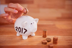 Composite image of digital image of new year 2017. Digital image of new year 2017 against human hand inserting coin in piggy bank vector illustration