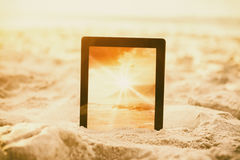Composite image of digital tablet kept on sand Royalty Free Stock Image