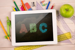 Composite image of digital tablet on students desk Stock Photography