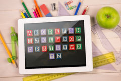 Composite image of digital tablet on students desk Royalty Free Stock Image
