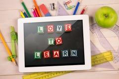 Composite image of digital tablet on students desk Stock Images
