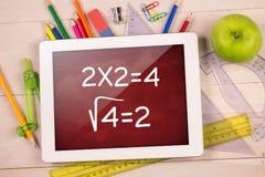 Composite image of digital tablet on students desk Stock Image