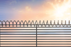 Composite image of digitallly generated image of barbed wire on fence Stock Photo