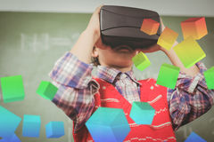 Composite image of digitally generated grey cubes floating. Digitally generated grey cubes floating against boy using a virtual reality device royalty free stock image