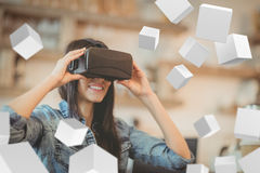 Composite image of digitally generated grey cubes floating. Digitally generated grey cubes floating against young woman using the virtual reality headset stock photos