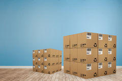 Composite image of digitally generated image of cardboard boxes. Digitally generated image of cardboard boxes against room with wooden floor Stock Images
