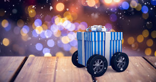 Composite image of digitally generated image of gift box with wheels Royalty Free Stock Photo