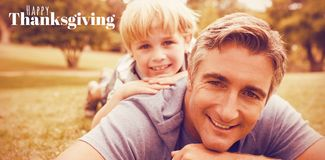 Composite image of digitally generated image of happy thanksgiving text. Digitally generated image of happy thanksgiving text against father and son lying on Royalty Free Stock Image