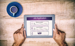 Composite image of digitally generated image of job application. Digitally generated image of Job Application  against hand holding on digital tablet over table Stock Images