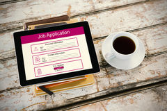 Composite image of digitally generated image of job application. Digitally generated image of Job Application  against overhead of tablet on desk Stock Images