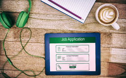 Composite image of digitally generated image of job application. Digitally generated image of Job Application  against view of a business desk Royalty Free Stock Photography