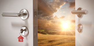 Composite image of digitally generated image of open door with house key. Digitally generated image of open door with house key against country scene stock images