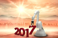 Composite image of digitally generated image of robotic hand holding red number Royalty Free Stock Photo