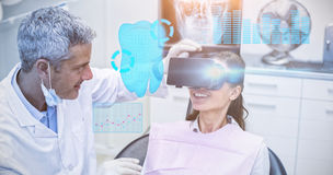 Composite image of digitally generated image of a teeth. Digitally generated image of a teeth against female patient virtual reality headset during a dental stock photo