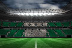 Composite image of digitally generated nigerian national flag. Digitally generated nigerian national flag against large football stadium Stock Image