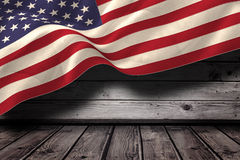 Composite image of digitally generated united states national flag. Digitally generated united states national flag against dark wooden room Royalty Free Stock Photography