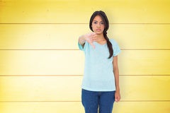 Composite image of disappointed brunette giving thumbs down Royalty Free Stock Photo