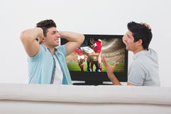 Composite image of disappointed soccer fans watching tv Royalty Free Stock Photo