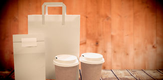 Composite image of disposable coffee cups and parcel bags. Disposable coffee cups and parcel bags  against wooden planks Stock Images