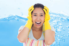 Composite image of distressed woman wearing apron and rubber gloves Royalty Free Stock Photos