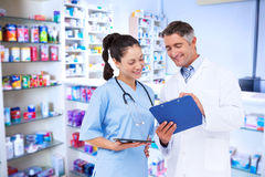 Composite image of doctor and nurse looking at clipboard Royalty Free Stock Image