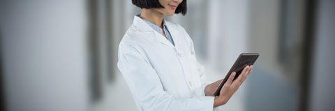 Composite image of doctor using digital tablet against white background. Doctor using digital tablet against white background against empty corridor in a stock photography