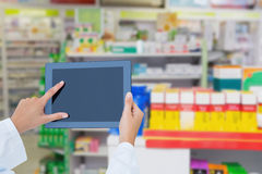 Composite image of doctor using tablet pc. Doctor using tablet pc  against close up of shelves of drugs Stock Images
