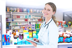 Composite image of doctor using tablet pc. Doctor using tablet pc against close up of shelves of drugs Stock Photography