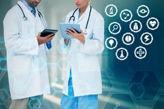 Composite image of doctors discussing something on clipboard. Doctors discussing something on clipboard against curved white room Royalty Free Stock Photos