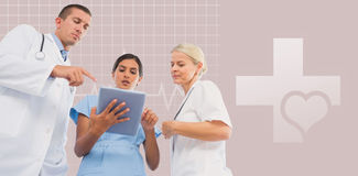 Composite image of doctors looking together at tablet. Doctors looking together at tablet against green background Stock Image