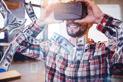 Composite image of dollars flying. Dollars flying against man using virtual reality headset Stock Photo