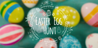 Composite image of easter egg hunt logo against white background. Easter Egg Hunt logo against white background against close-up of painted easter eggs stock images