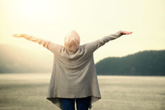 Composite image of elder woman stretching. Elder woman stretching  against scenic view of lake and mountain Stock Image