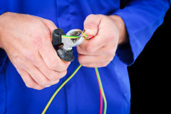 Composite image of electrician cutting wire with pliers Stock Images