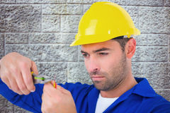 Composite image of electrician wearing hard hat while cutting wire Royalty Free Stock Images