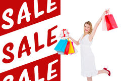 Composite image of elegant blonde with shopping bags and gifts Royalty Free Stock Photography