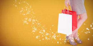Composite image of elegant brunette posing with shopping bags Stock Photo