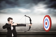 Composite image of elegant businessman shooting bow and arrow Stock Photo