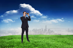 Composite image of elegant businessman standing and using binoculars Royalty Free Stock Images