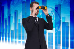 Composite image of elegant businessman standing and using binoculars Royalty Free Stock Photos